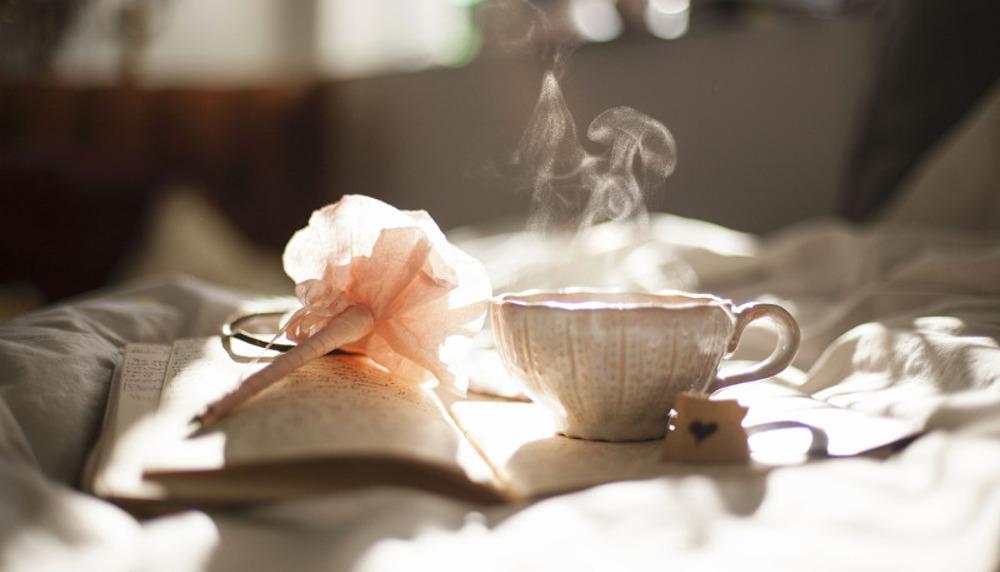 buch-mit-kaffee-und-stift-auf-bett